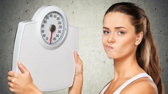 体重計を見て悩む女性の画像