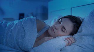 ベッドで眠る女性の画像