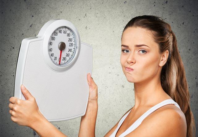 ダイエットに悩む女性と体重計の画像