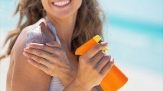 日焼け止めを持つ女性の画像